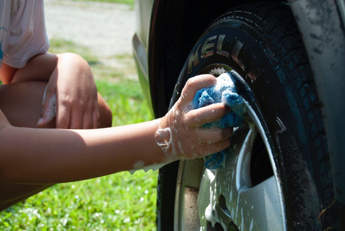 Picturecar tire being washed with a rag